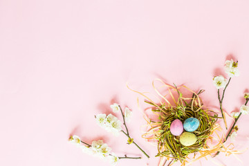 Painted eggs in nest and floral branches lying on pink paper background. Easter decoration. Flat lay. Top view.