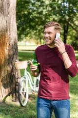 cheerful man talking on smartphone while talking on smartphone