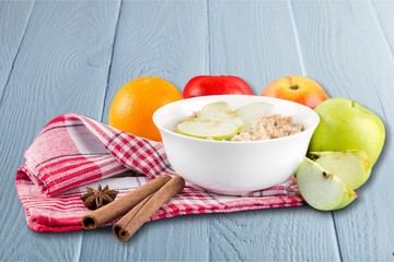 Raw oats in bowl and fruit salad, apples on the wooden table