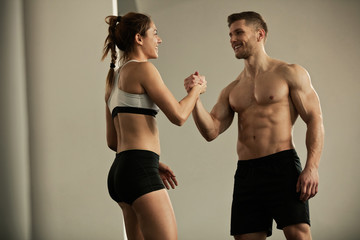 Happy athletic couple greeting each other in a gym. Wall mural