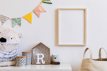 Stylish scandinavian child room with mock up photo poster frame on the white wall. Cute modern interior of playroom with boxes, teddy bear, toys.  wooden accessories and colorful flags. Real photo.