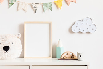 Stylish and modern scandinavian newborn baby interior with mock up photo or poster frame on the white shelf. Toys, teddy bear, wooden car and hanging cotton colorful flags and star. Template. Blank.