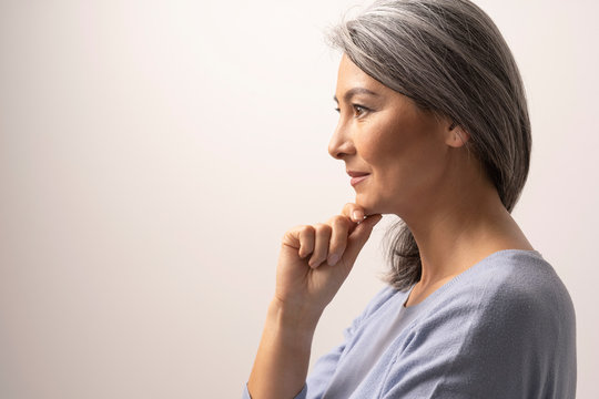 Pensive woman is touching chin and slightly smiles