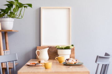 Stylish and modern interior of kitchen space with small wooden table with mock up photo frame, beautiful plants, design cups and tasty dessert. Scandinavian room decor with kitchen accessories.