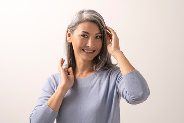 Smiling Asian woman touches her grey hair