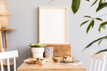 Stylish and sunny interior of kitchen space with small wooden table with mock up photo frame, design cups and tasty dessert. Scandinavian room decor with kitchen accessories and beautiful plants.