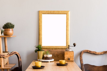 Retro and stylish interior of kitchen space with small wooden table with gold mock up photo frame, design cups and vintage chairs.Scandinavian room decor with kitchen accessories and beautiful plants.