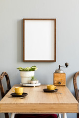 Retro and stylish interior of kitchen space with small wooden table with brown mock up photo frame, design cups and vintage chairs.Scandinavian room decor with kitchen accessories and beautiful plant.