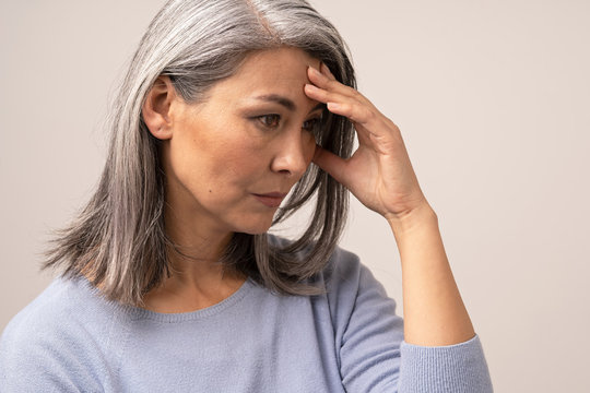 Mature Asian woman touches her forehead in distress