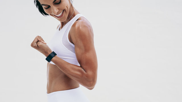 Close up of a smiling fitness woman looking at her hand