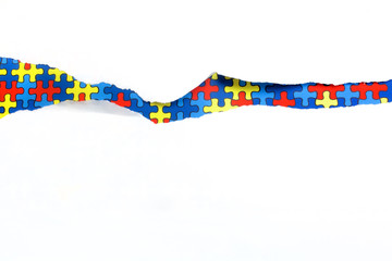 torn white paper on multicolored puzzle background. Cocept for autism awareness day. Break barriers together for autism.