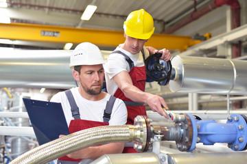 Gruppe Monteure bei der Instandhaltung in der Industrie // Mechanics repair a machine in a modern industrial plant - profession and teamwork