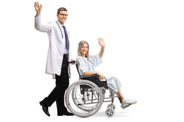 Young male doctor and a female patient in a wheelchair waving