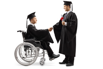 Male graduate student in a wheelchair shaking hand with a male graduate student standing and holding a diploma