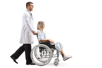Young male doctor pushing a woman in a wheelchair