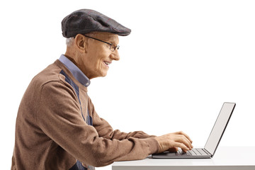 Senior man sitting and typing on a laptop computer