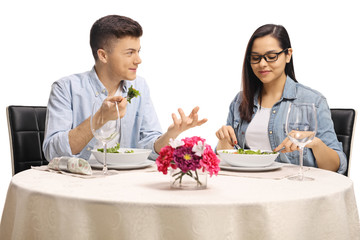 Young male and female eating a salad at a restaurant table and talking