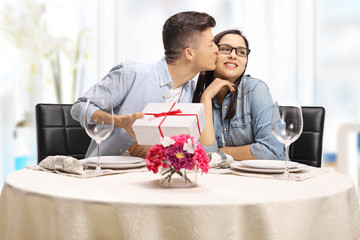 Young guy kissing a girl and giving a present at a restaurant table