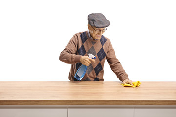 Elderly man cleaning a wooden counter
