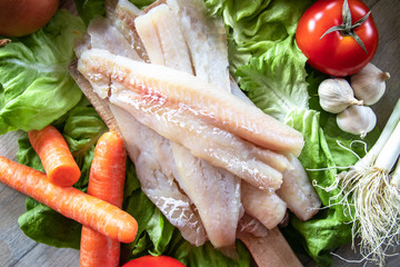 Raw hake fish fillets pieces with organic fresh vegetables in the background