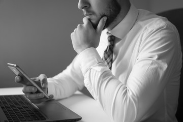 Financial business. Holding smartphone in hand. Light background. Young bearded businessman. Office work with a laptop. Businessman work with computer on table in office work.
