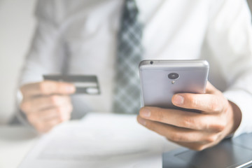 Young businessman with a bank credit card in his hands. Online trading on the currency exchange. Smartphone and Internet Commerce. Payment of goods online. Online payments through the phone.