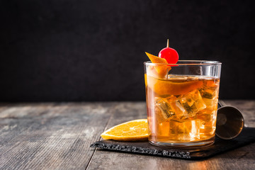 Old fashioned cocktail with orange and cherry on wooden table. Copyspace Wall mural