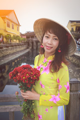 beautiful women in Ao Dai Vietnam traditional dress holding a branch of red flowers