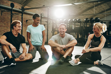 Smiling friends talking together on a gym floor after exercising