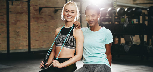 Smiling women sitting on a box after their gym workout