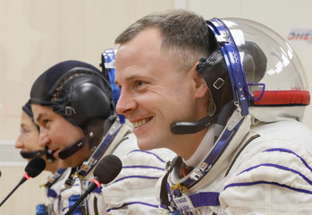 The International Space Station (ISS) crew members talk after donning space suits shortly before their launch at the Baikonur Cosmodrome