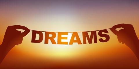 Concept du rêve et de l'imagination, avec deux mains qui tiennent une guirlande sur laquelle est écrit le mot rêve, devant un ciel ensoleillé.