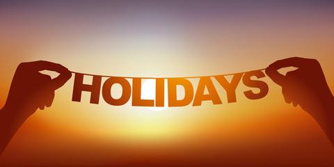 Concept du bonheur de partir en vacances avec deux mains qui tiennent une guirlande sur laquelle est écrit le mot vacances devant un ciel ensoleillé.