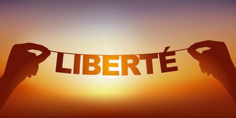 Concept de l'esprit libre, avec deux mains qui tiennent une guirlande sur laquelle est écrit le mot liberté devant un ciel ensoleillé.