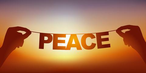 Concept de la paix et la tranquillité, avec deux mains qui tiennent une guirlande sur laquelle est écrit le mot paix, devant un ciel ensoleillé.