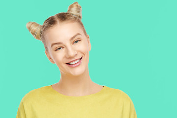 Portrait of a cute happy blonde girl with a funny hairstyle horns, rejoices, having fun, laughing and smiling toothy wide in yellow clothes on a green background