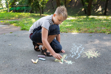 Young kid holding piece of chalk and drawing sea water, tropical island with palms and sun on pavement of sidewalk outdoors at city park. Child drawing summer sunny beach. Horizontal color photography