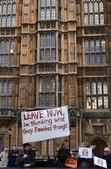Pro-Brexit protesters hold up signs outside the Houses of Parliament in London