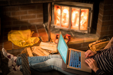 Cozy home. Pretty young woman working on laptop computer near the fireplace.
