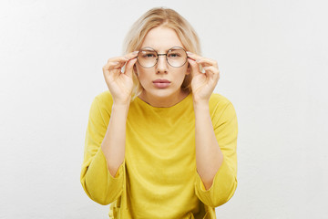 Portrait of a beautiful young woman with spectacles, looking curiously at you, squinting, trying to look closer. Girl with poor eyesight in yellow T-shirt posing on a white background in the studio