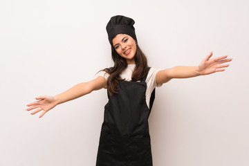 Teenager chef  over white wall presenting and inviting to come with hand