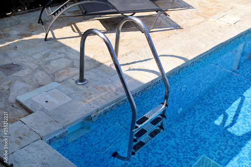 Handrail on pool. Swimming pool with stair at tropical ...