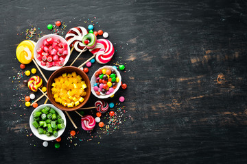 Background of colored candies and lollipops. Sweets. On a black background. Top view. free copying space.