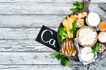 Food with calcium. A variety of foods rich in calcium: cheese, milk, parmesan, sour cream, fish, almonds, parsley, garlic, broccoli. On a white wooden background. Top view. Free copy space.