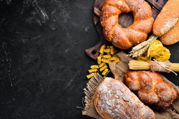 Wall Mural - Gluten free food. Bread, pasta and flour on a black stone background. Top view. Free space for your text.