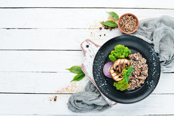 quinoa with mushrooms and vegetables on a plate. Top view. Free space for your text.