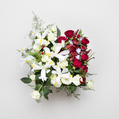 Flower arrangement. Original bouquet of flowers and greens isolated on soft gray background.High quality photo.
