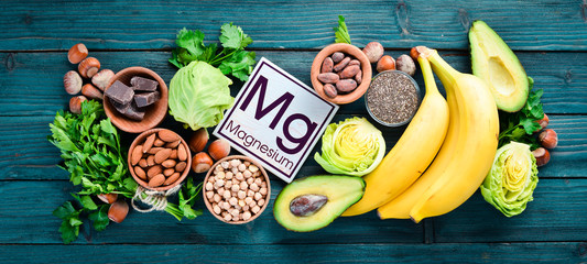 Foods containing natural magnesium. Mg: Chocolate, banana, cocoa, nuts, avocados, broccoli, almonds. Top view. On a blue wooden background.