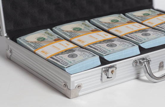 Open suitcase with hundred dollar bills stacks