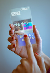 Woman hand holding transparent smartphone and touching the screen. Social media, business, technology and people concept